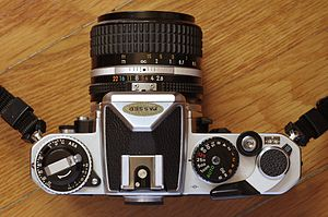 Nikon FE - Nikon FE top plate showing the film-speed and exposure compensation dials on the left, and shutter speed dial on the right.