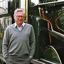 Colour photograph of man in grey pullover standing close to dark green steam locomotive (Great Western Railway King Edward I), with copper pipes showing on side of locomotive.