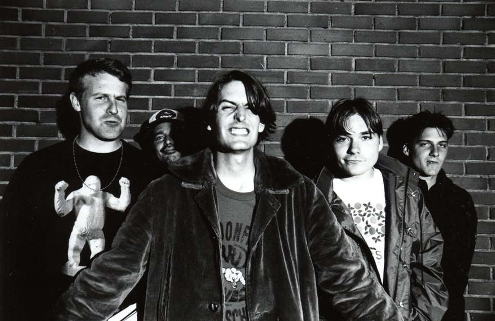 A black and white photograph of five members of the group Pavement standing in front of a brick wall