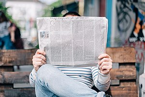 Person reading a newspaper (Unsplash).jpg