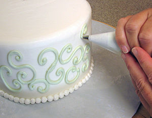 Cake decorating - Buttercream swirls are piped onto the sides of a cake with a pastry bag