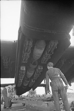 405 Maritime Patrol Squadron - Armourers check over a mixed bomb load of three 1,000-lb MC bombs and small bomb containers (SBCs) filled with 30-lb incendiary bombs, loaded into the bomb-bay and wing cells of a Handley Page Halifax Mark II of 405 Squadron RCAF at RAF Pocklington, England