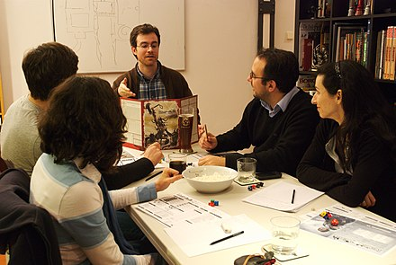 A Gamemaster explaining to the players in a table-top RPG Role playing gamers (III).jpg