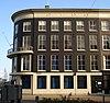 foto van Pand met afgeronde hoek, drie verdiepingen en hoofdgestel met in het fries panelen, waarboven rijk geprofileerde kroonlijst