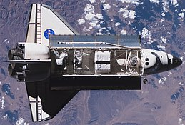 A space shuttle, with its payload bay full of equipment, seen orbiting over a cloudy sky above a mountainous region of the Earth.