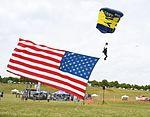 Sailor flies the American flag while as he parachutes onto the field during the Lynchburg Regional Air Show. (27192415165).jpg