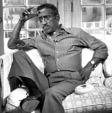 Black-and-white photograph of an elderly African-American man wearing a striped shirt, grey trousers, a watch and various jewelry, sitting hunched on a sofa with a sombre expression.