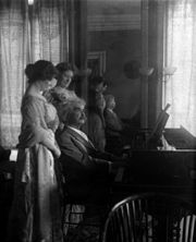 Photograph of Mark Twain playing piano, with his daughter Clara and her friend behind him