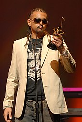 A picture of a man wearing a beige jacket and holding a silver award statue