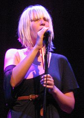 A blonde woman singing with her eyes closed