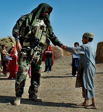 7th Special Forces Group (United States) - A soldier from A Co, 1st Bn, 7th SFG(A) gives an Afghan boy a coloring book in Kandahar Province during a meeting with local leaders, September 2008