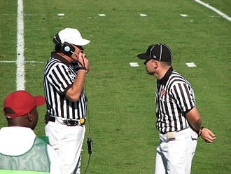 Replay review in gridiron football - Referee (left) talking with the replay official
