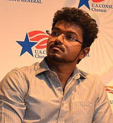 A photo of Vijay looking at his right.