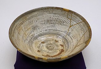 Kintsugi - Repair work (right) on Mishima ware hakeme-type tea bowl with kintsugi gold lacquer, 16th century (Ethnological Museum of Berlin)