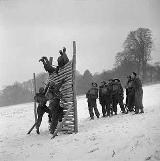 Royal Hampshire Regiment - Men of the 2/4th Battalion, Hampshire Regiment scale an obstacle during 'toughening up' training in wintry conditions at Wateringbury in Kent, 20 January 1942.