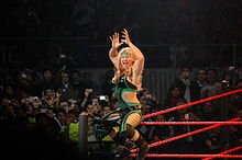 A blonde woman sits on the turnbuckle of a wrestling ring, stradding the ring post, and facing the crowd while posing with her hands in the air. She is wearing a green and black catsuit with the sides of the torso removed to bare part of her midriff.
