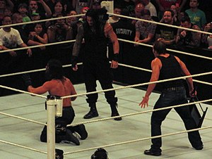 Payback (2014) - Seth Rollins, on his knees, being confronted by his former teammates Dean Ambrose and Roman Reigns after he betrayed them