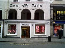 A shop front on the ground floor, above which at the first floor level are three round-headed arches. Above these is the inscription The Old Arches and the date 1274AD