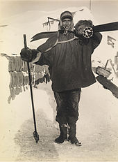 Man, standing, wearing a smock, heavy trousers and boots. He has a ski stick in his right hand, a pair of skis strapped on his back, and is carrying a rounded bundle on his shoulder. Behind him on the ground is assorted polar equipment.