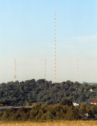 Mühlacker radio transmitter - Radio towers of Transmitter Mühlacker in September 2004 (from left to the right): Steel framework tower for directional radio, height: 93 m, built in 2004; reflector mast for medium wave with antennas for mobile phone services, height: 80 m, year of construction 1977; Main transmission mast for medium wave and FM, height: 273 m, built in 1950; reflector mast for medium wave, height: 130 m, built in 1954. Between the main transmission mast and the reflector mast there are the two small grey masts, which can be hardly seen in the picture and which carry the shortwave antenna