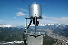 A metallic cylinder sits atop a square platform raised by two bolts. A prism connected to cables monitors the mountain for movement.