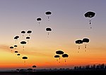 U.S. Army paratroopers assigned to the 1st Batallion, 503rd Infantry Regiment, 173rd Airborne Brigade Combat Team glide toward a landing zone after jumping from an Air Force C-130 Hercules aircraft as part 131210-F-MO006-259.jpg