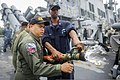 U.S. Navy Damage Controlman 2nd Class Endulk Hailu, right, demonstrates firefighting procedures to Philippine sailors during a crash and salvage drill aboard the guided missile destroyer USS John S. McCain (DDG 140627-N-UN259-175.jpg