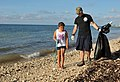 U.S. Navy Master-at-Arms 2nd Class Justin Sosa and his daughter look for trash to pick up at Truman Annex at Naval Air Station Key West, Fla., Sept 130921-N-YB753-049.jpg