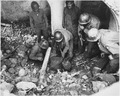 U.S. soldiers begin to uncover a comrade who has been buried in the debris of a building hit by a bomb during a Nazi... - NARA - 196315.tif