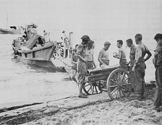 1st Mountain Battery (Australia) - A 3.7 inch mountain howitzer of the 1st Mountain Battery being dismantled before being loading onto a Japanese motor barge (captured at Milne Bay).