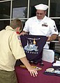 US Navy 040429-N-6268K-025 Postal Clerk 1st Class Joseph Crozier sells command ball caps and shirts to Boy Scouts touring the guided missile cruiser USS Philippine Sea (CG 58).jpg