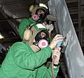 US Navy 041130-N-7816R-032 Aviation Structural Mechanic 3rd Class Adams David of Paducah, Ky., front, and Airman Brandon Davis of Lexington Ky., sand corrosion at the top of a vertical stabilizer on an F-A-18C Hornet.jpg