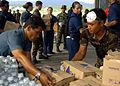 US Navy 050123-N-8801B-151 Indonesian Air Force personnel and U.S. Navy Sailors assigned to the amphibious assault ship USS Essex (LHD 2), transport food, clothing and relief supplies from a warehouse to awaiting U.S. Navy heli.jpg