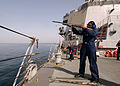 US Navy 050206-N-5345W-027 A Sailor fires a .12-gauge shotgun while shooting skeet from the forecastle during a holiday routine aboard the Arleigh Burke-class guided missile destroyer USS Mason (DDG 87).jpg