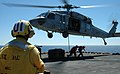 US Navy 060405-N-6403R-012 Aviation Ordnanceman 3rd Class William T. Hinson and Aviation Ordnanceman Man 3rd Class Kyle Baker clear a MH-60S Seahawk helicopter during a vertical replenishment.jpg