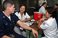 US Navy 060531-N-3931M-012 Nurses for the Philippine National Red Cross, takes a temperature reading and other vital information from Navy Petty Officer 3rd Class Christopher Orr.jpg