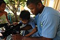 US Navy 070717-N-9421C-095 Mass Communication Specialist Seaman Patrick House demonstrates how to operate a video camera to a child at Hoi Mai Orphanage in Da Nang, Vietnam.jpg