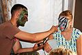 US Navy 080802-N-1424C-460 hip's Serviceman Seaman Steven Day paints camouflage face paint on a visitor.jpg