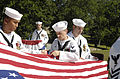 US Navy 080908-N-8467N-001 Electronics Technician (Chief Select) Chase Smith, assigned to Naval Submarine School at Naval Base New London, Conn. cuts off the first strip of the American flag in a flag retirement ceremony.jpg