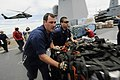 US Navy 110312-N-3005P-181 Hull Technician 2nd Class Seneca Jernigan, left, and Yeoman 3rd Class Steven Tai move pallets of humanitarian assistance.jpg
