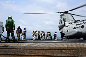 US Navy 120212-N-WV964-152 Mock non-combatant evacuation operation (NEO) participants exit a CH-46 Sea Knight helicopter aboard the forward-deploye.jpg