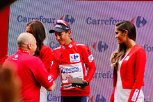 A photograph of Esteban Chaves, wearing the race leader's red jersey, shaking hands with an official, with podium girls either side