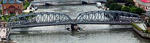 A bridge of two gray metal spans, curving segmentally above, crossing a river, seen from an upward angle