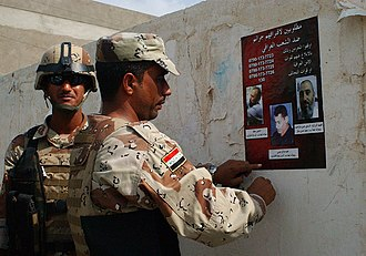 Subversion - Iraqi troops put up a poster of wanted insurgents.