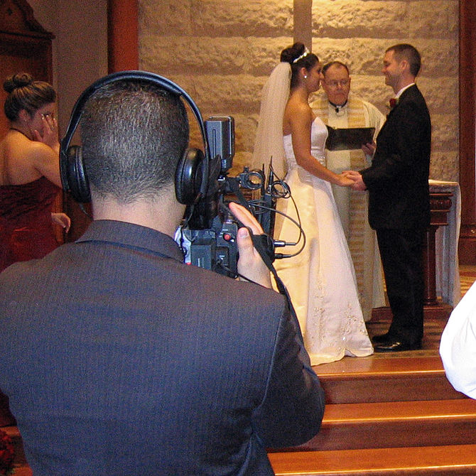 English: A wedding videographer recording the ...