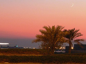 Ramadan - A crescent moon can be seen over palm trees at sunset in Manama, marking the beginning of the Islamic month of Ramadan in Bahrain