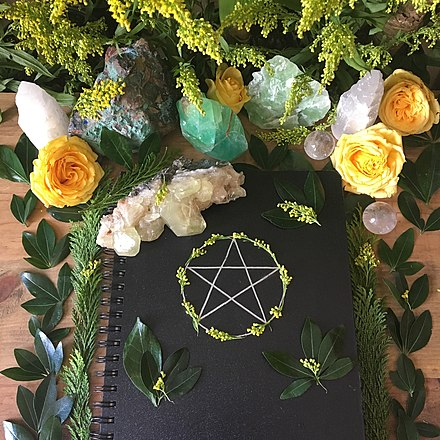 A 'Book of Shadows', sitting on a wiccan altar, alongside plants and crystals. Wiccan 'Book of Shadows'.jpg
