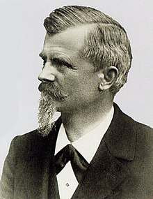 Black-and-white photo of a middle-aged man with a beard and moustache