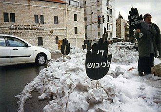 """Women in Black - Women in Black staging a protest in Paris Square, Jerusalem, with the distinctive black stop signs calling """"Stop the occupation"""" in three languages"""