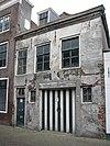 foto van Pand met verdieping en schilddak. Gepleisterde gevel met houten kroonlijst en bovenvensters met zesruitsschuiframen